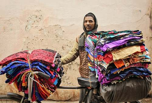 varanasi man standing beside bicycle with clothes india