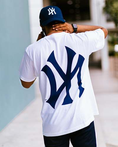 clothing man wearing white and blue New York Yankees t-shirt walking while touching his neck human