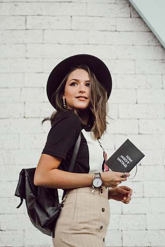 clothing woman in black blazer and brown dress holding booklet while looking into left side and smiling hat