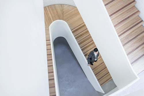 london person stepping down on brown wooden stairs aerial photography wood