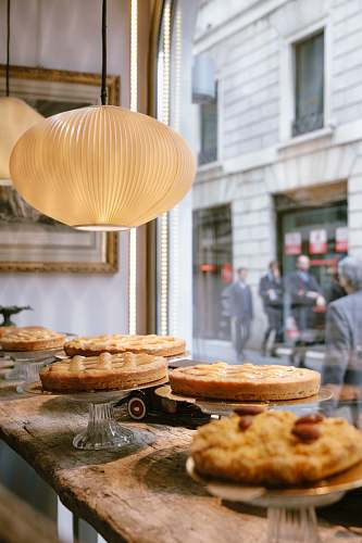 human round white pendant lamp above assorted cakes on display person