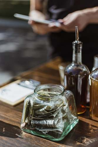 drink banknotes in clear glass container on wooden surface liquor