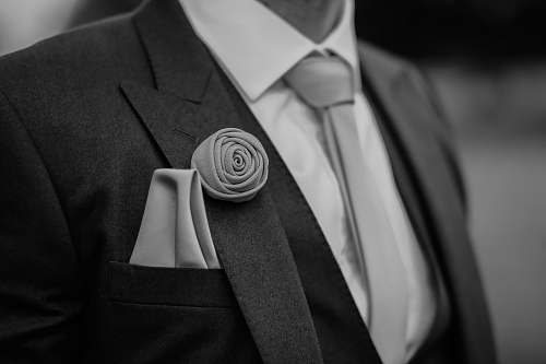 suit greyscale photo of man wearing peak lapel suit jacket clothing