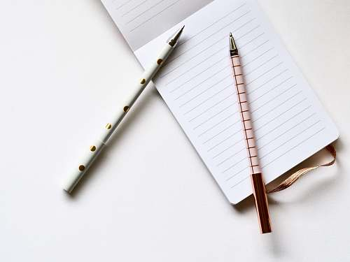 paper two white and beige pens on white paper notepad