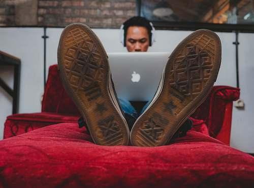 clothing man using MacBook on sofa cowboy boot