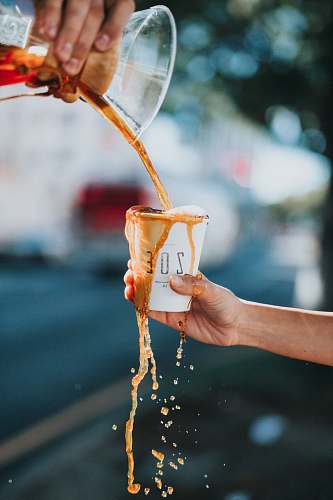 coffee person holding white ZOE brand paper cup drink