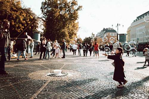 city girl in black coat trying to hold bubbles on air during daylight downtown