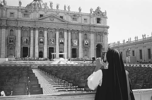 black-and-white nun taking photo of building architecture