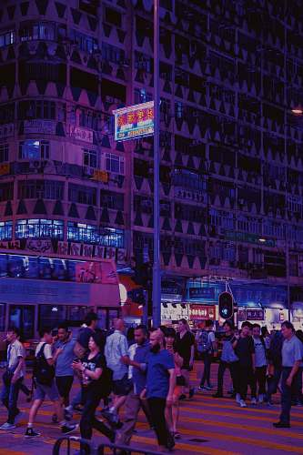 city people standing beside concrete buildings during night time downtown
