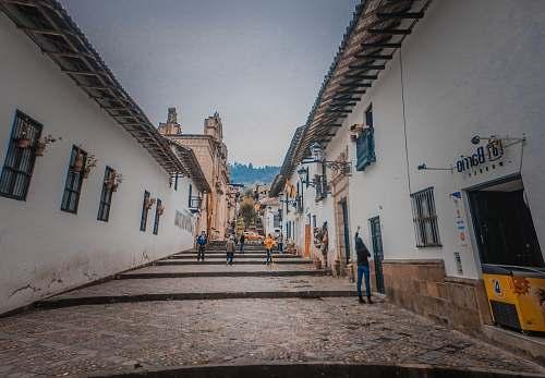 path people walking between white houses during daytime walkway