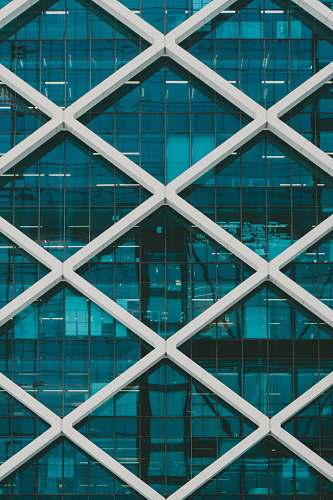 architecture teal and white high-rise building at daytime window