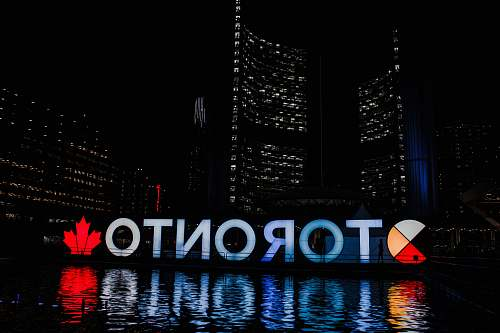 photo city Toronto sign reflecting on body of water at night metropolis free for commercial use images