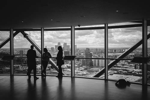 black-and-white people standing inside city building skyline