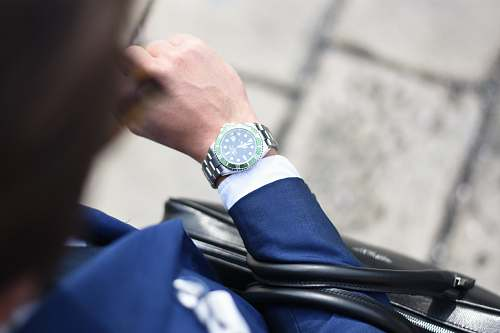 watch person looking at silver-colored analog watch suit