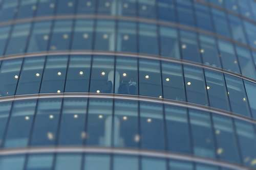 building selective focus photograph of person standing near building glass curtain grey