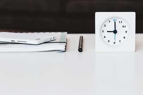 grey white desk clock near pen and book black-and-white