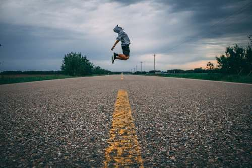 road time-lapse photo of person jumping at the middle of the road lac santé