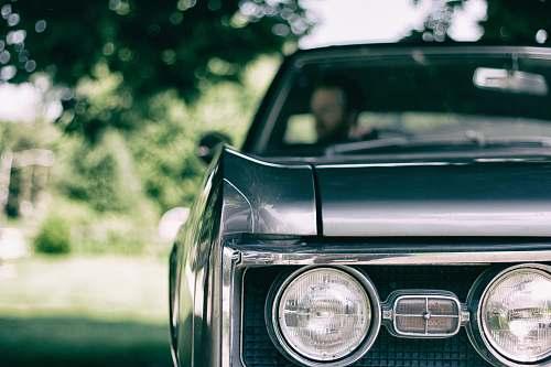 headlight man inside black muscle car automobile
