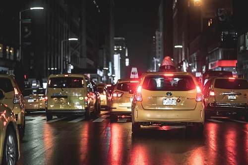 automobile vehicles on road beside buildings during nighttime transportation