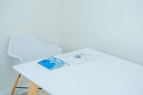 furniture blue covered book on white table with armchair in front united kingdom