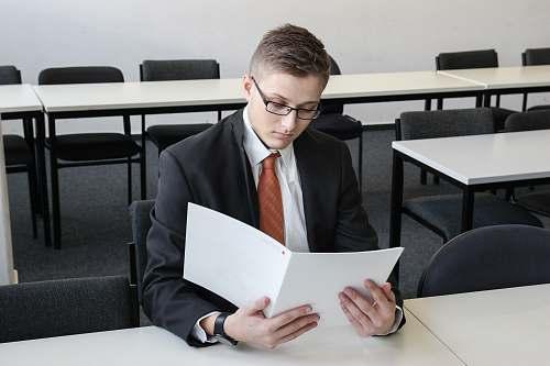 furniture man holding folder in empty room tie