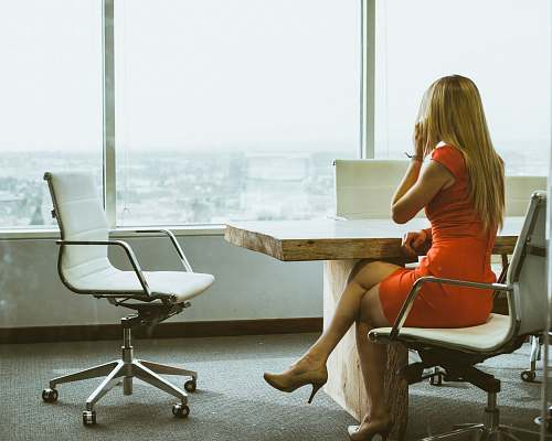business woman talking through mobile phone while sitting on swivel armchair woman