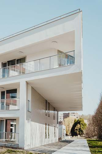 photo urban white concrete residential building near trees housing free for commercial use images