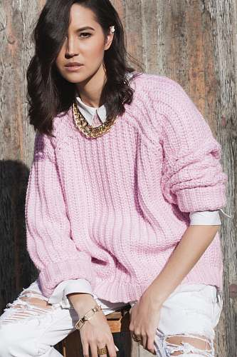apparel women in pink knitted sweater sitting by woode wall sleeve