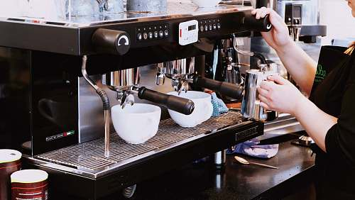 barista person holding black espresso maker machine
