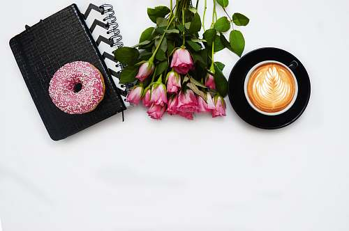 pink red rose flowers, pink dough nut graphic book and black ceramic cup kiev