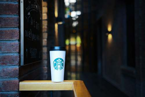 brick Starbucks coffee on top of wooden rail blackboard