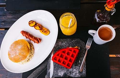 fork sausage between fried banana and pancake breakfast