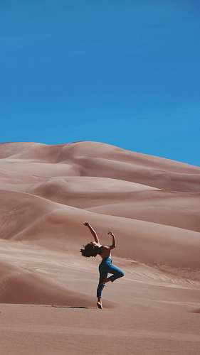 desert woman standing on right foot and raising hands at the bottom of sand dunes during daytime dance pose