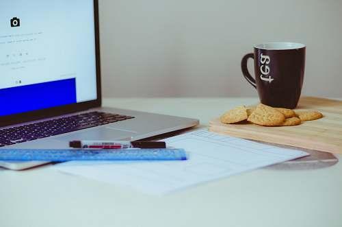 biscuit pastry beside ceramic mug cookie
