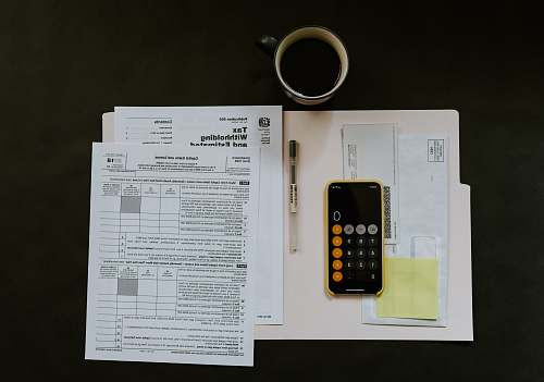 cell phone black Android smartphone near ballpoint pen, tax withholding certificate on top of white folder mobile phone
