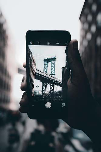 phone grayscale photography of person holding iPhone capturing bridge mobile phone