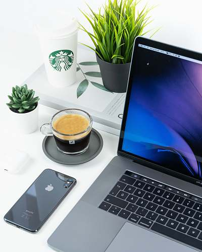 pc laptop beside iPhone and coffee in cup on table computer