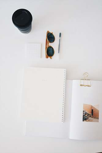 glasses flat lay photography of paper, sunglasses, cup, and pen notebook