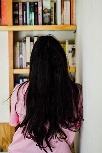 human woman leaning on wall looking at bookshelf person