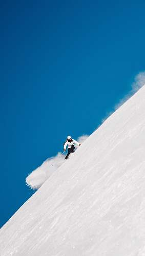 blue person snowboarding on mountain cliff norway