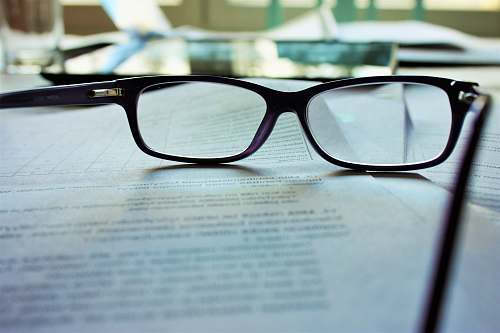 reading black-framed eyeglasses on white printing paper book