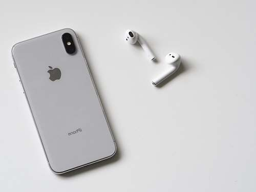 black-and-white silver iPhone X and Apple EarPods phone
