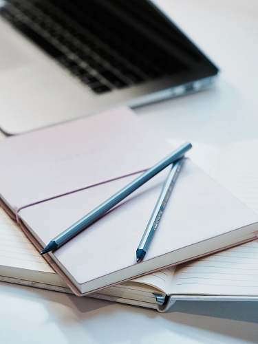notebook close-up photography of two pencils on closed pink covered book on desk near MacBook Air in a well-lit room pen