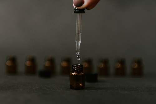 person clear drop bottle