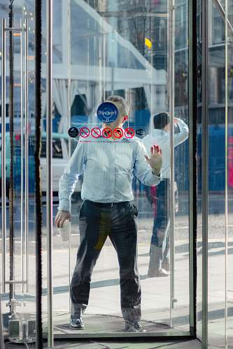 person man leaning on glass door people