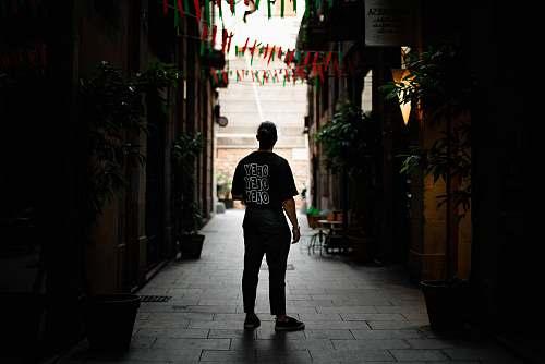 person man standing in alley between buildings people