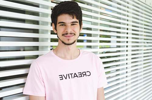person man standing near window apparel