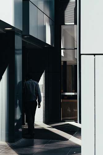 person man walking on gray tiled pathway inside building people