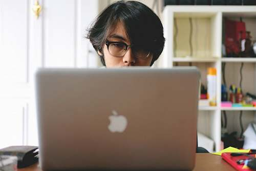 person man wearing eyeglasses while using silver Macbook near wooden cubby shelf inside room people