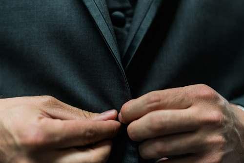 person person holding black suit jacket button suit